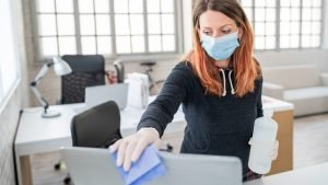 Woman wearing mask cleaning laptop at the office
